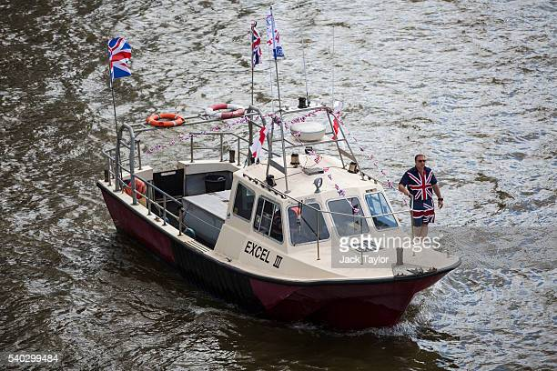 A man wearing a Union Jack shirt and shorts stands on board a boat from the 'Fishing for Leave' campaign group during a flotilla along the Thames...