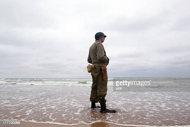 A man wearing a US World War II uniform walks on the beach of SaintLaurent sur Mer western France on June 6 during a ceremony to mark the 67th DDay...
