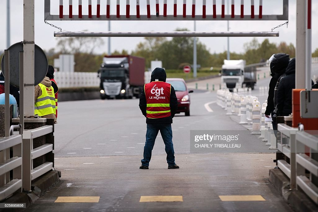 A man wearing a waistcoats of the French CGT Trade Union stands guard as he blocks the road at a toll booth on the Normandy Bridge in Le Havre, northwestern France, on April 29, 2016 during a demonstration against the new labour draft-law. / AFP / CHARLY