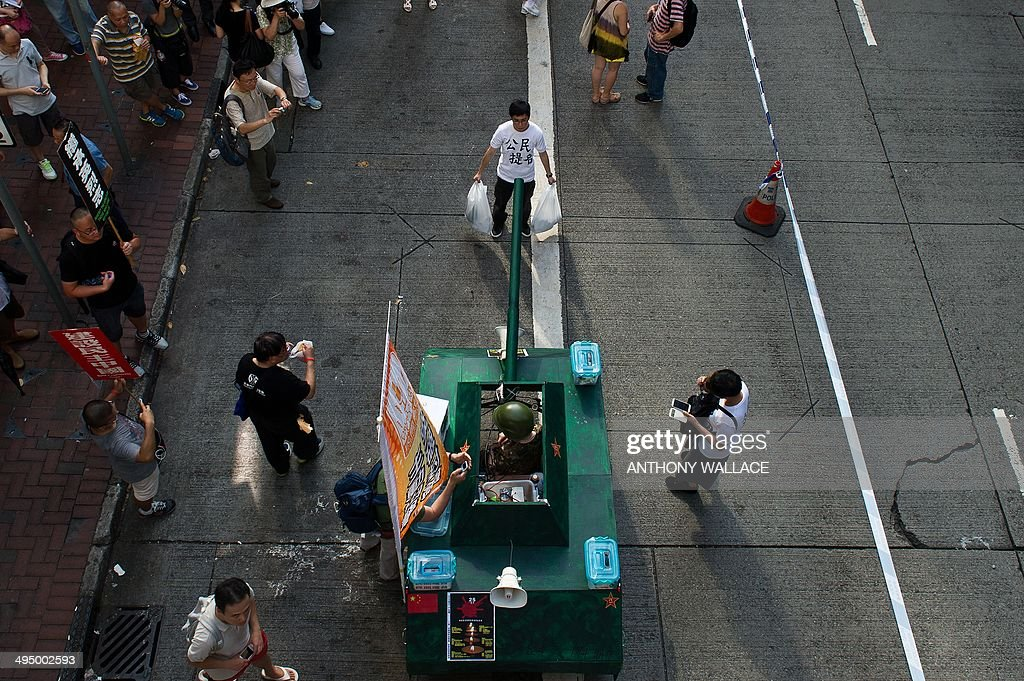A man wearing a white shirt and carrying a shopping bag in each hand stands facing a mock Chinese tank to recreate the famous 'Tank Man' scene that...