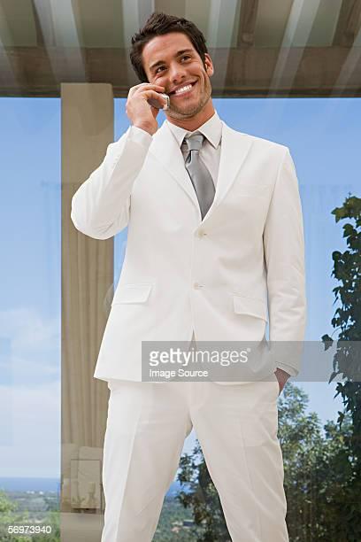 Mann in einem weißen Badeanzug auf dem Mobiltelefon
