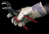 Man wearing a work glove and holding a pair of pliers