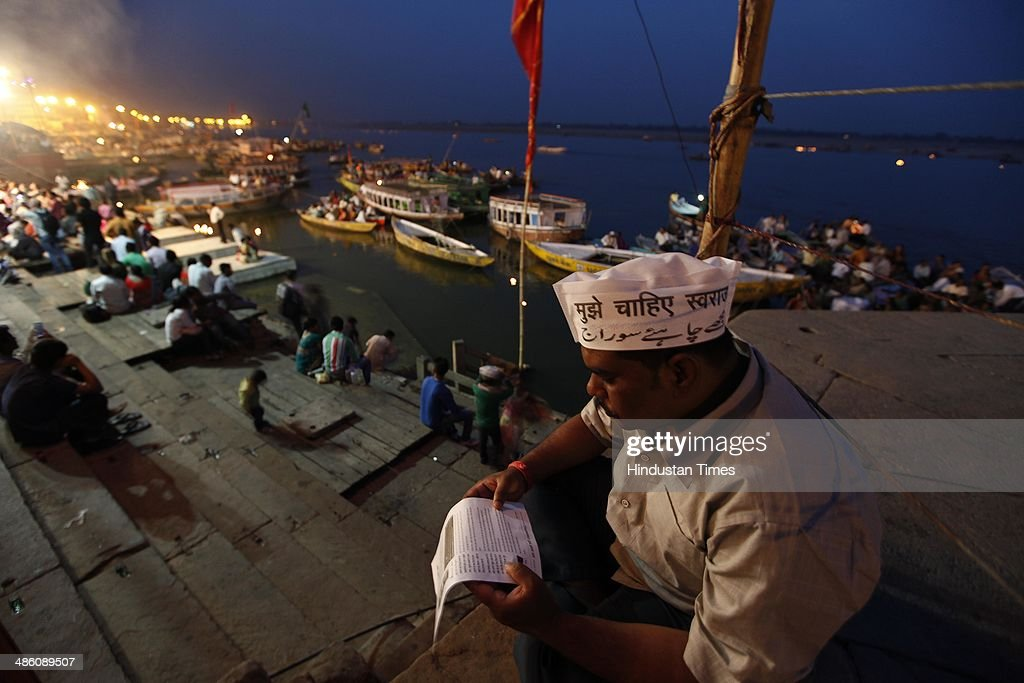 A man wearing AAP cap and reading pamphlet distributed by AAP volunteers during an election campaign Dashashavmedh Ghat on April 22, 2014 in Varanasi, India. Narendra Modi will file his nomination from Varanasi on April 24. His rival contestants are Aam Aadmi Party leader Arvind Kejriwal, Ajay Rai of the Congress and Kailash Chaurasia of the Samajwadi Party
