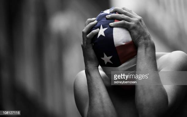 Man WEaring American Flag As Mask And Holding Head