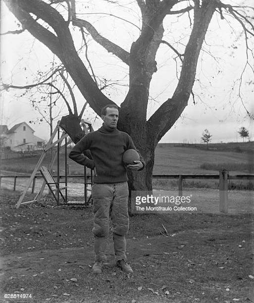 Man wearing American football clothing with quilted trousers and poloneck jumper andpadded shin pads standing in field in front of a swing seat...