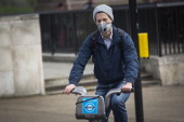 A man wearing an antipollution mask rides a bicycle at Hyde Park Corner on April 2 2014 in London England Dust from the Sahara combined with...