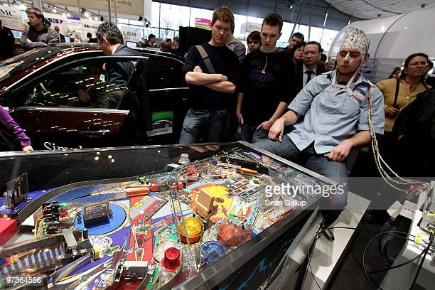 A man wearing an EEG brain scanning apparatus on his head plays a pinball game solely through willing the paddles to react with his brain at the...
