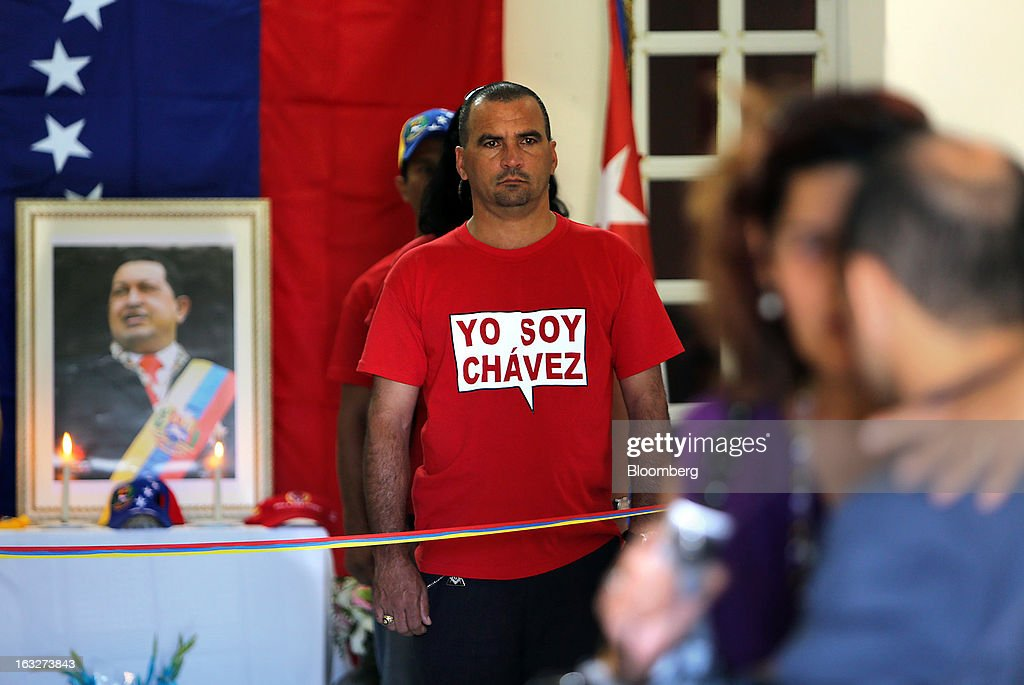 A man wearing an 'I Am Chavez' tee shirt stands with other mourners during a ceremony commemorating the death of Venezuelan President Hugo Chavez in the Venezuelan Embassy in Havana, Cuba on Wednesday, March 6, 2013. Cuba's government praised Chavez's goal of uniting the people of Latin America and pledged loyalty to the continuation of his Bolivarian Revolution, according to the statement in the state-run Granma website. Photographer: Noah Friedman-Rudovsky/Bloomberg via Getty Images