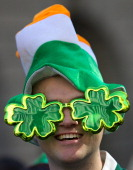 A man wearing an Irish flag hat t and fourleaf clover sunglasses attends a St Patrick's Day parade in Central London on March 16 2014 Some 400000...