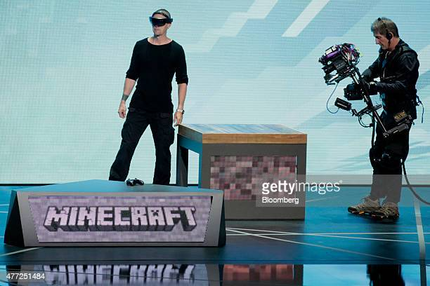 A man wearing an Oculus VR Inc headset demonstrates playing the Minecraft video game during the Microsoft Corp Xbox event ahead of the E3 Electronic...