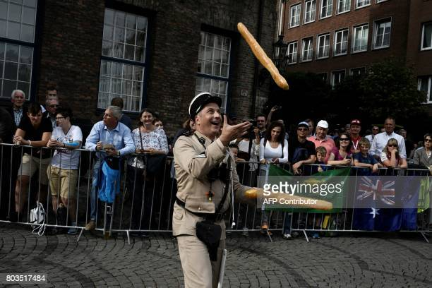 A man wearing an old French gendarme uniform juggles with fake baguettes as he performs during the parade of the team presentation ceremony in...