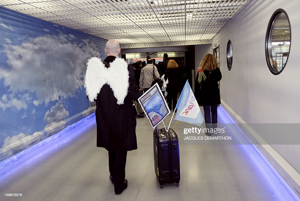 A man wearing 'angels wings' takes part in a demonstration with pilots and cabin crew members of European airline companies, on January 22, 2013 at Roissy Charles-de-Gaulle airport, in Roissy-en-France outside Paris, as part of a strike of European pilots. AFP PHOTO JACQUES DEMARTHON