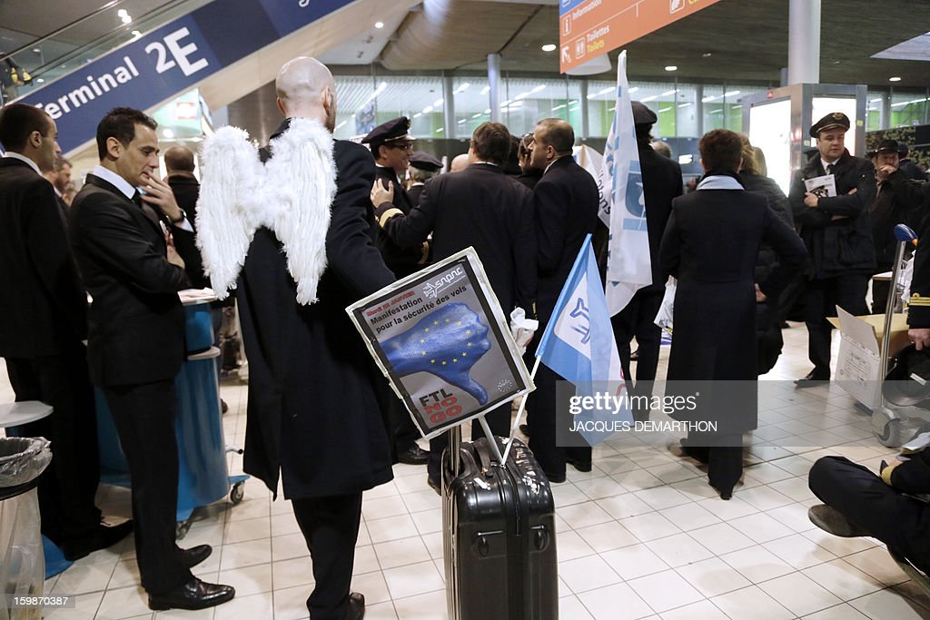 A man wearing 'angels wings' takes part in a demonstration with pilots and cabin crew members of European airline companies take part in a demonstration, on January 22, 2013 at Roissy Charles-de-Gaulle airport, in Roissy-en-France outside Paris, as part of a strike of European pilots.