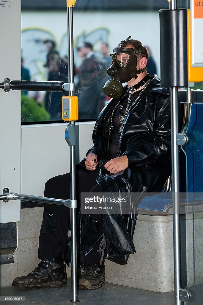 A man wearing black clothing and a gas mask sits in the tramway car on the second day of the annual Wave-Gotik Treffen, or Wave and Goth Festival, on May 18, 2013 in Leipzig, Germany. The four-day festival, in which elaborate fashion is a must, brings together over 20,000 Wave, Goth and steam punk enthusiasts from all over the world for concerts, readings, films, a Middle Ages market and workshops.