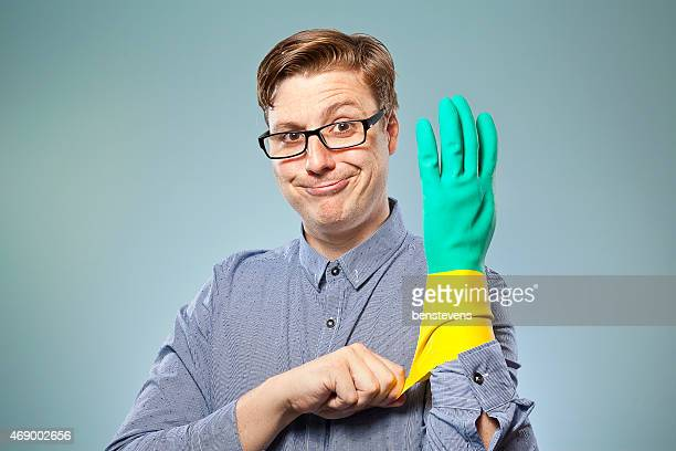 Man wearing black glasses pulling on rubber glove