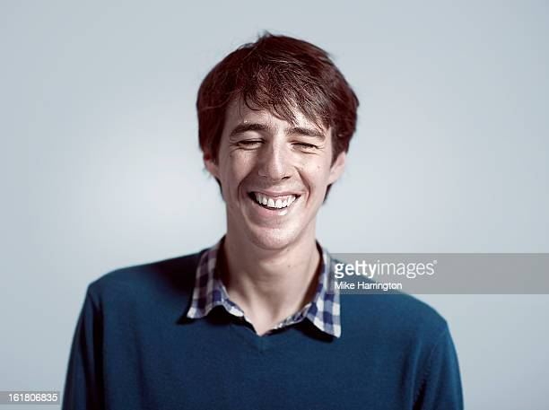 Man wearing blue V-neck jumper laughing.