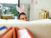 Man wearing bunny ears in office, desk divder in foreground