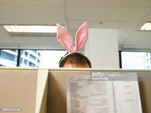 Man wearing bunny ears in office, high section