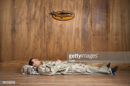 Man Wearing Camouflage Sleeping on Floor in Wood-paneled Room