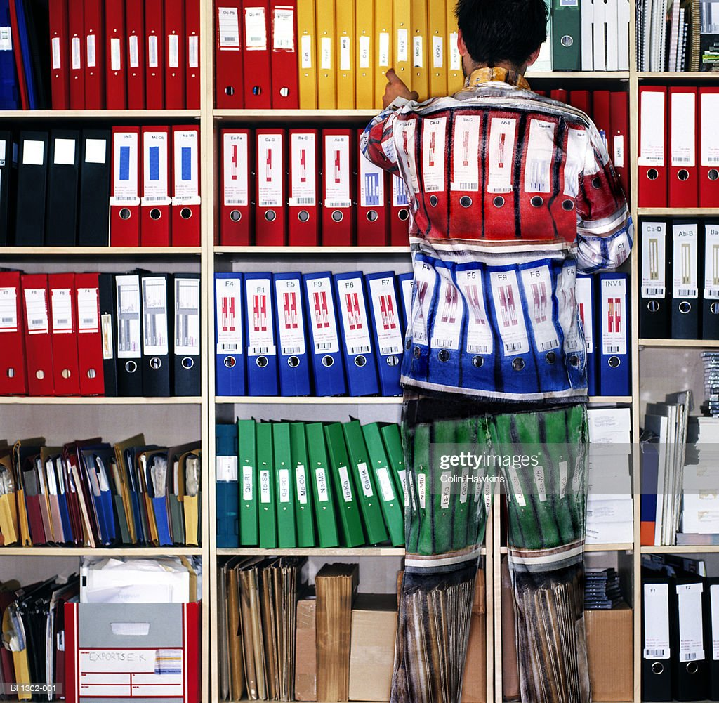Man wearing camouflage suit matching shelves of folders