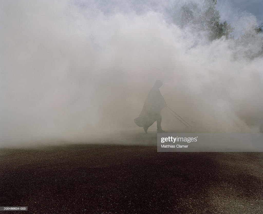 Man wearing cape, pushing lawn mower through smoke : Stock Photo