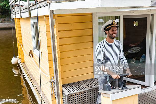 Man wearing captains hat having a trip on a house boat