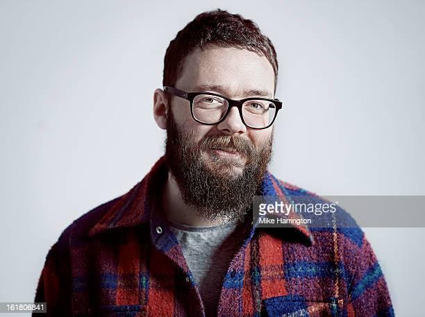 Man wearing check shirt wearing beard smiling.