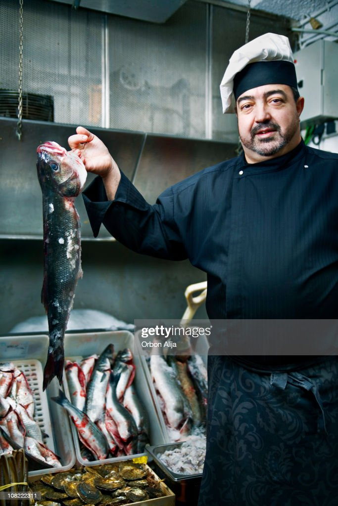 Man Wearing Chef's Uniform Displaying Fish : Stock Photo