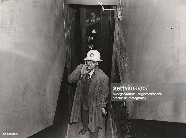 A man wearing civilian defense air raid warden hat shouts up to apartment residents from the bottom of a stairwell New York 1945 Photo by Weegee...
