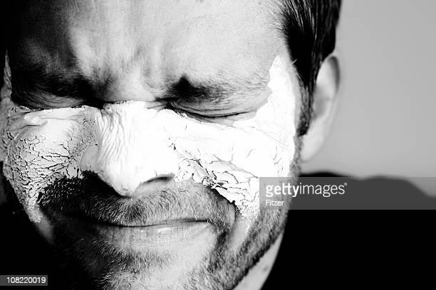 Mann mit Ton-Gesichtsmaske und Wincing