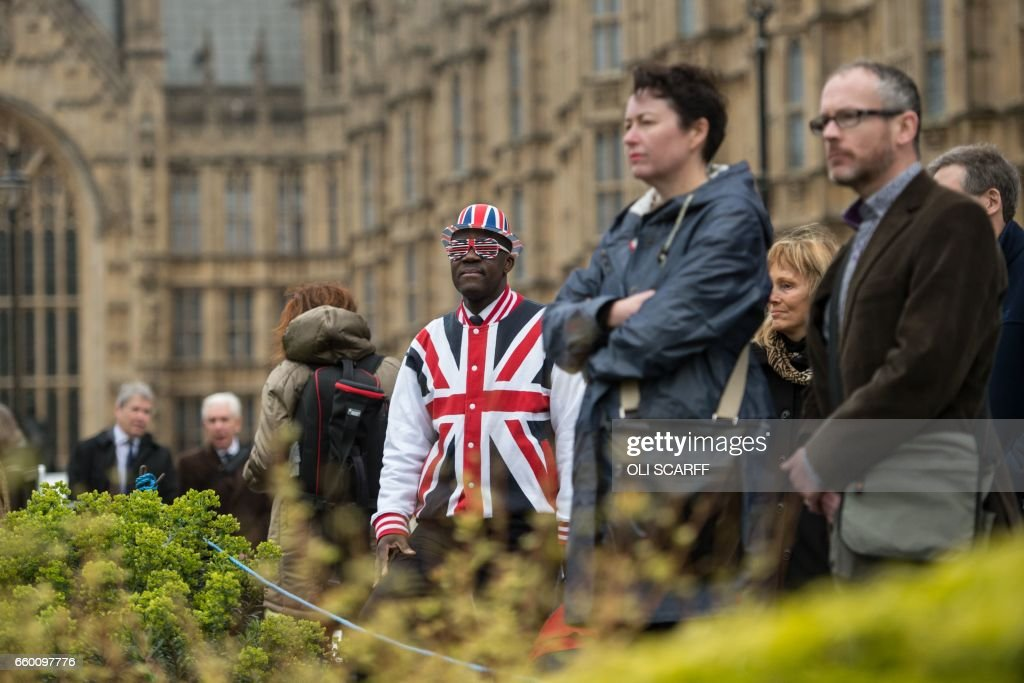 A man wearing clothing featuring the Union flag stands in front of the Houses of Parliament in London, on March 29, 2017, shortly before British Prime Minister Theresa May announced to the House of Commons that Article 50 of the Lisbon Treaty had been triggered, formally starting Britain's withdrawl from the European Union (EU). Britain formally launched the process for leaving the European Union on March 29, a historic move that has split the country and thrown into question the future of the European project. /