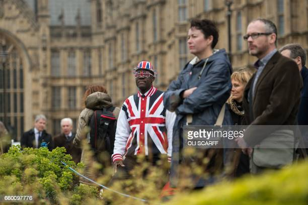 A man wearing clothing featuring the Union flag stands in front of the Houses of Parliament in London on March 29 shortly before British Prime...