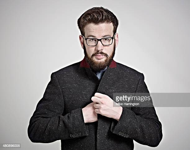 Man wearing coat and glasses looking to camera.