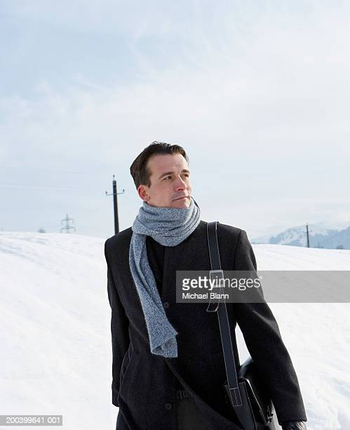 Man wearing coat and scarf walking in snow covered landscape