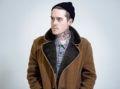 Man wearing coat and woolly hat looking to side.