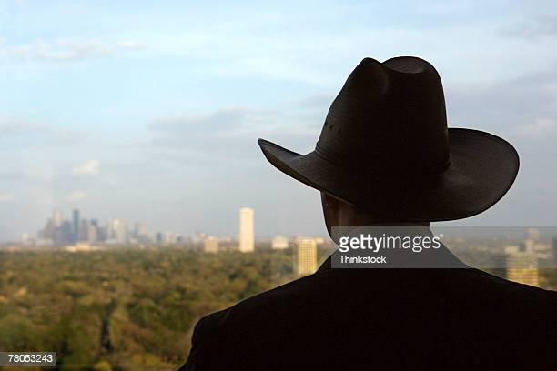 Man wearing cowboy hat gazing at skyline