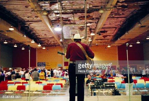 Man wearing cowboy hat, playing guitar in auditorium, rear view