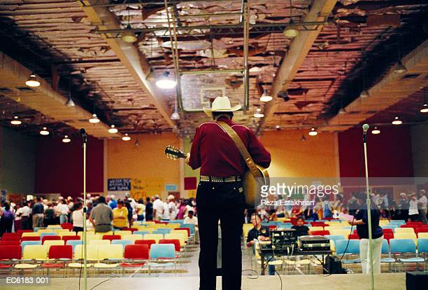 Man wearing cowboy hat, playing guitar in auditorium, rear view