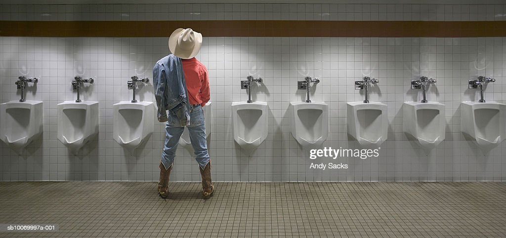 Man wearing cowboy hat standing at urinal, rear view (digital composite)