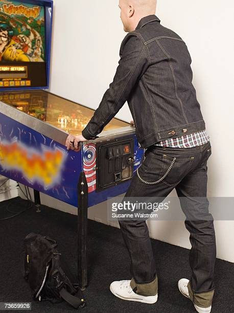 A man wearing denim playing flipper.