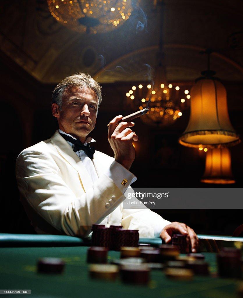 Man wearing dinner jacket smoking cigar in casino, portrait