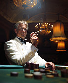Man wearing dinner jacket smoking cigar in casino, portrait