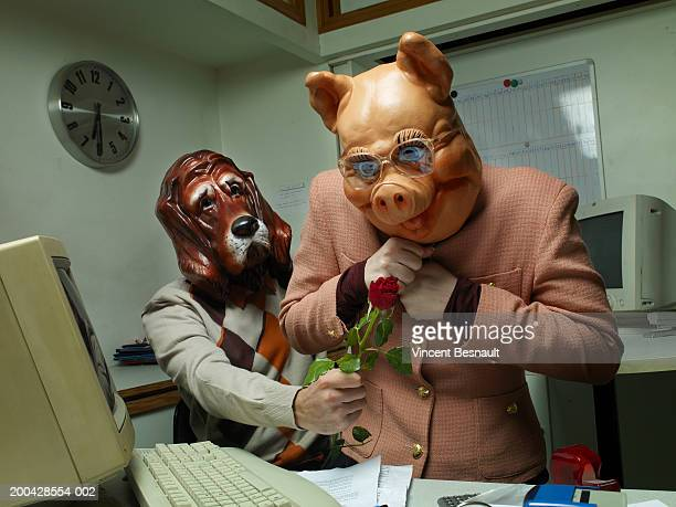 Man wearing dog mask giving rose to woman in pig mask at office desk