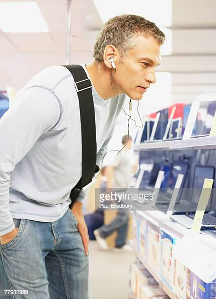 Man wearing earbuds looking at laptops in store