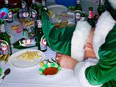 Man wearing elf costume, head on table by food