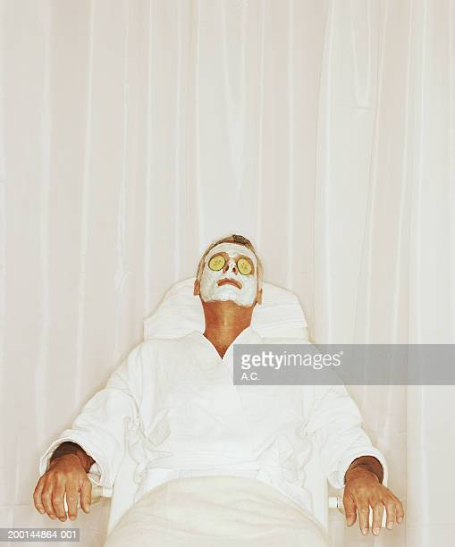 Man wearing face mask, cucumber slices on eyes