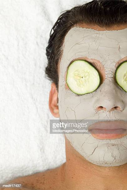 Man wearing face pack with cucumber slices on eyes, close-up