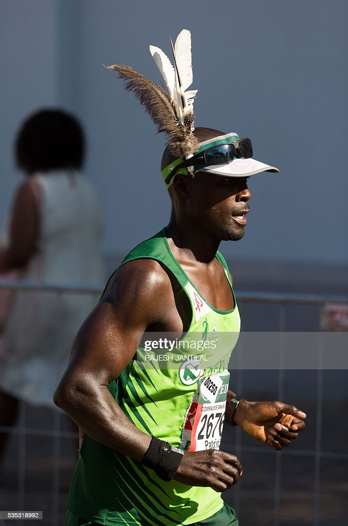 A man, wearing feathers on his head, runs along with other 21,000 competitors from South Africa and abroad, the 89,2 kilometres ultra distance Comrades Marathon from Pietermaritzburg to Durban on May 29, 2016. It is regarded as one of the most gruelling ultra marathons in the world. / AFP / RAJESH