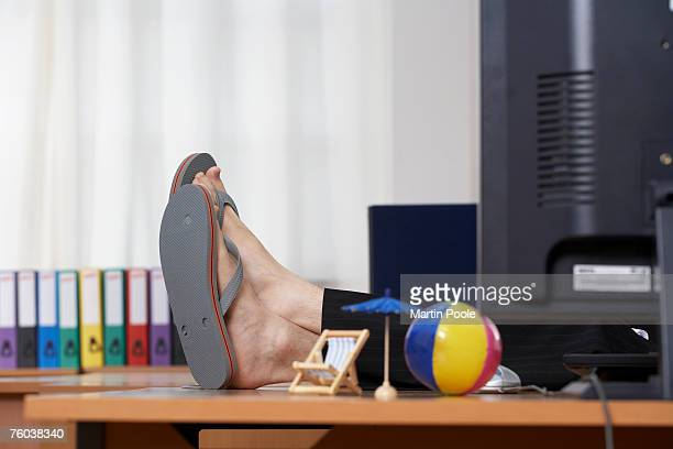 Man wearing flip flops with feet up on desk in office, low section