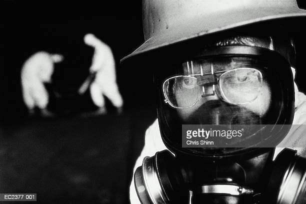Man wearing gas mask,working on hazardous waste site,portrait (B&W)